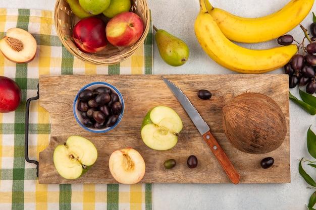 Bovenaanzicht van fruit als half gesneden appel perzik en druiven bessen kokosnoot met mes op snijplank en mandje van perzik appel op geruite doek met banaan druif op witte achtergrond