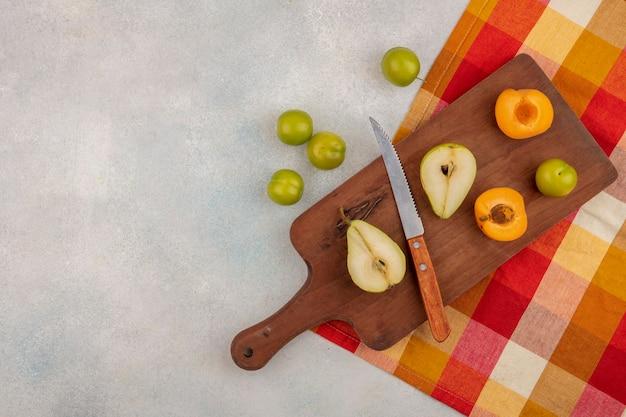 Bovenaanzicht van fruit als half gesneden peer en abrikoos met mes op snijplank en pruimen op witte achtergrond met kopie ruimte