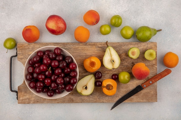 Bovenaanzicht van fruit als half gesneden peer pruim abrikoos met mes en kom met kers op snijplank en patroon van peer pruim abrikoos op witte achtergrond