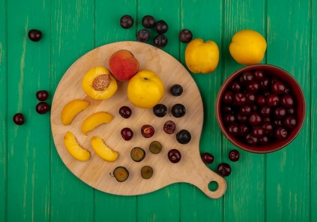 Bovenaanzicht van fruit als hele half gesneden abrikozen en sleedoorn bessen met mes op snijplank en kom met kersen op groene achtergrond