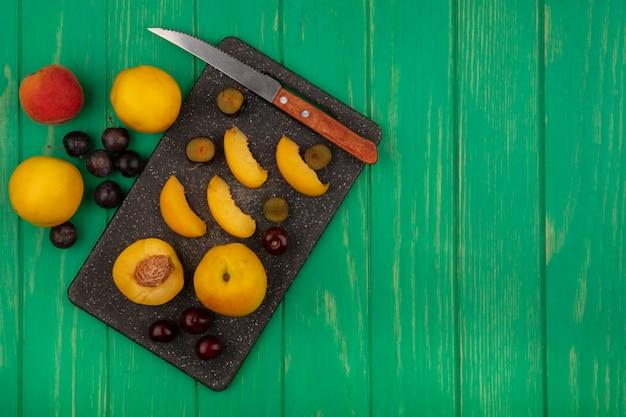 Bovenaanzicht van fruit als hele half gesneden abrikozen en sleedoorn bessen met mes op snijplank en op groene achtergrond met kopie ruimte