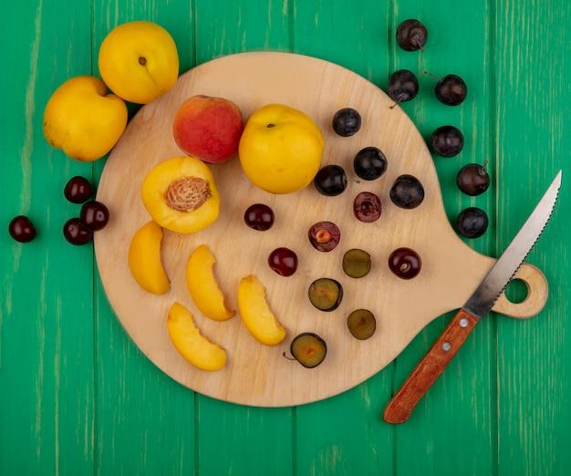 Bovenaanzicht van fruit als hele half gesneden abrikozen en sleedoornbessen met mes op snijplank en op groene achtergrond