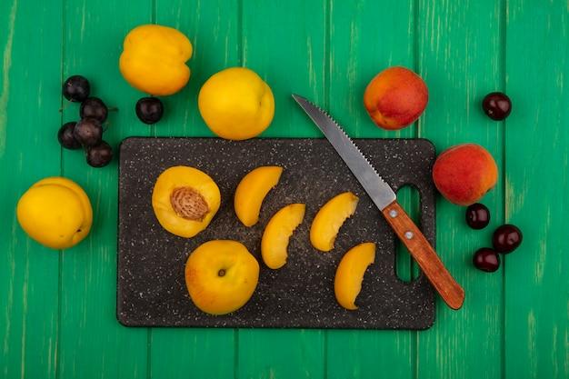 Bovenaanzicht van fruit als hele half gesneden abrikozen met mes op snijplank en hele met sleedoorn bessen op groene achtergrond