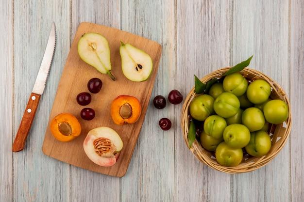 Bovenaanzicht van fruit als kersen en half gesneden abrikozenpeer en perzik op snijplank met mandje met pruimen en mes op houten achtergrond