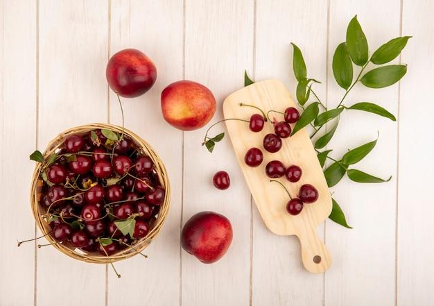 Bovenaanzicht van fruit als kersen in mand en op snijplank met perziken en bladeren op houten achtergrond