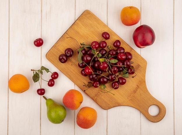 Bovenaanzicht van fruit als kersen op snijplank met perziken en peren op houten achtergrond