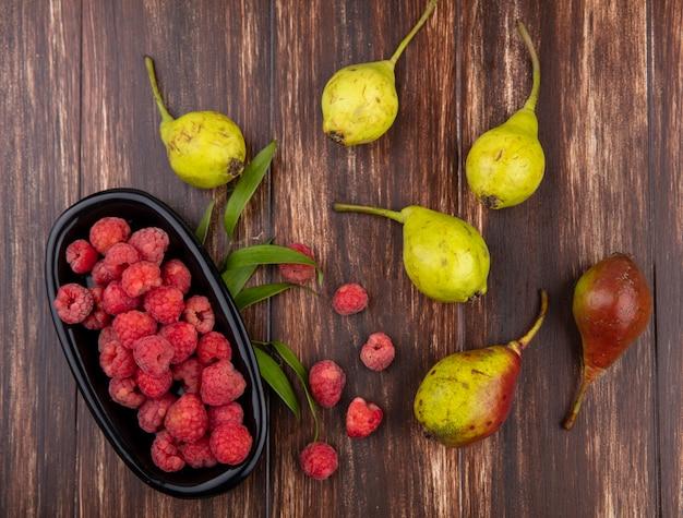 Bovenaanzicht van fruit als kom van frambozen en perziken met bladeren op houten oppervlak