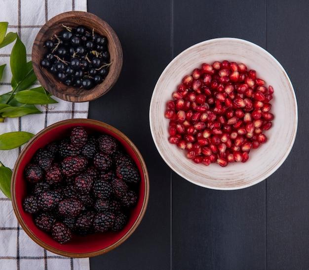 Bovenaanzicht van fruit als kommen sleedoorn en braambes met bladeren op geruite doek en kom granaatappelbessen op zwarte ondergrond
