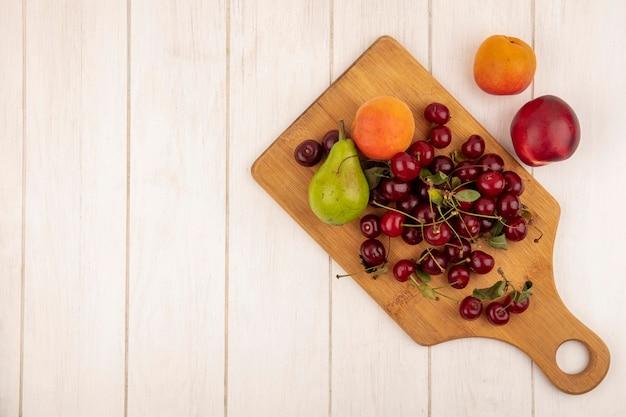 Bovenaanzicht van fruit als peer abrikoos en kersen op snijplank en op houten achtergrond met kopie ruimte