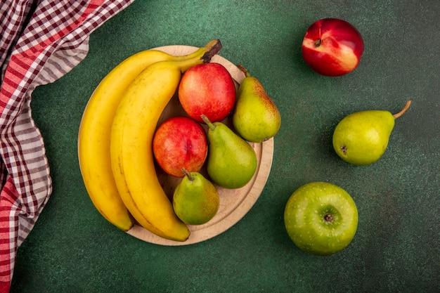 Bovenaanzicht van fruit als perzik-peer banaan op snijplank met appel en geruite doek op groene achtergrond