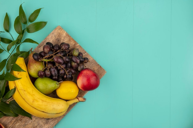 Bovenaanzicht van fruit als perzik peer citroen druif banaan met bladeren op snijplank op blauwe achtergrond met kopie ruimte
