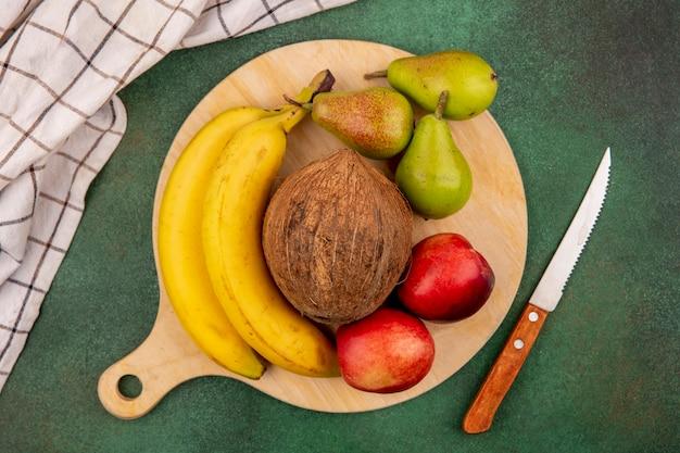 Bovenaanzicht van fruit als perzik peer kokos banaan op snijplank met mes en geruite doek op groene achtergrond