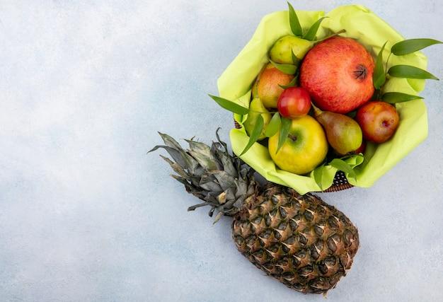 Bovenaanzicht van fruit als perzik van de pruimappel en granaatappel in mand met ananas op witte oppervlakte met exemplaarruimte