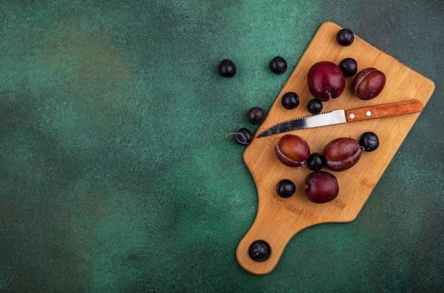 Bovenaanzicht van fruit als plukken en druivenbessen met mes op snijplank op groene achtergrond met kopie ruimte
