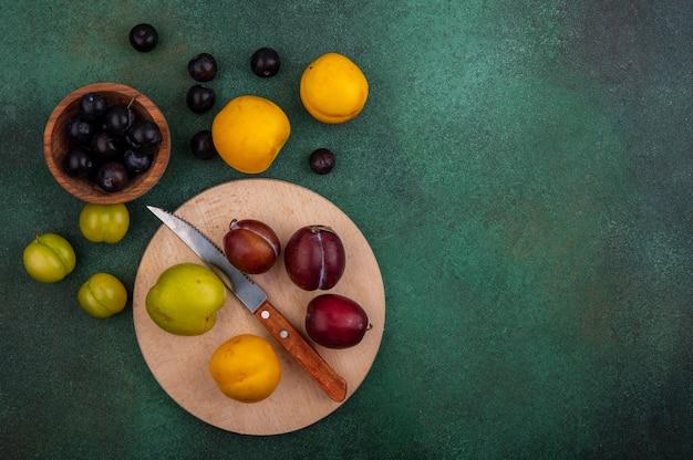 Bovenaanzicht van fruit als plukken en nectacot met mes op snijplank en druiven bessen in kom met pruimen nectacots en druiven bessen op groene achtergrond met kopie ruimte