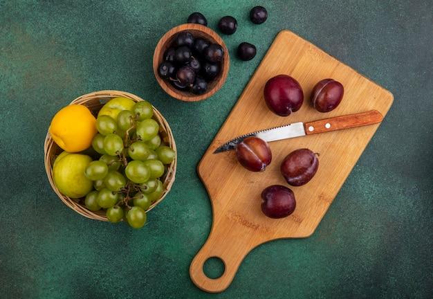 Bovenaanzicht van fruit als plukken met mes op snijplank en nectacots plukken druif in mand met druiven bessen in kom en op groene achtergrond