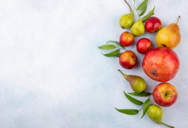 Bovenaanzicht van fruit als pruim appel perzik en granaatappel op witte ondergrond