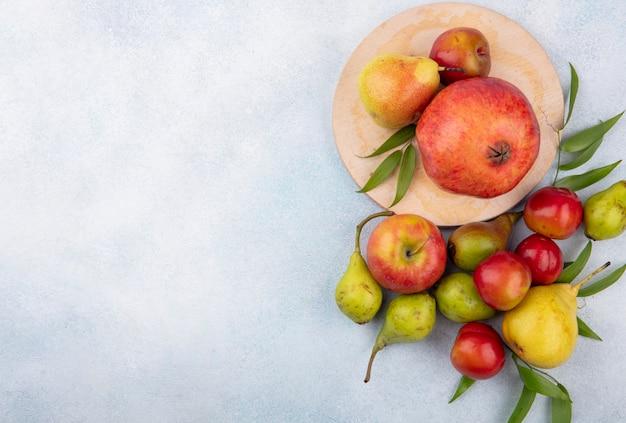 Bovenaanzicht van fruit als pruim perzik en granaatappel op snijplank en met apple op wit oppervlak met kopie ruimte