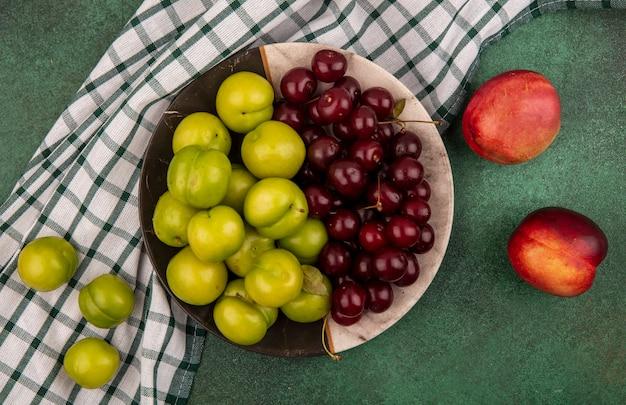 Bovenaanzicht van fruit als pruimen en kersen in plaat op geruite doek met perziken op groene achtergrond