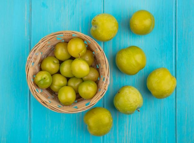Bovenaanzicht van fruit als pruimen in mand en patroon van groene plukken op blauwe achtergrond