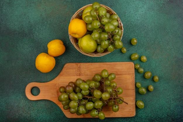 Bovenaanzicht van fruit als tros druiven op snijplank en nectacot pluot en druif in mand met druiven bessen op groene achtergrond