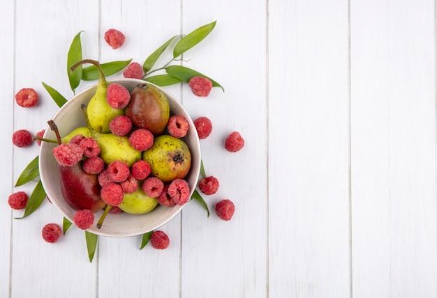 Bovenaanzicht van fruit in kom met bladeren op houten oppervlak