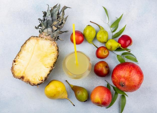 Bovenaanzicht van fruit met ananassap op witte ondergrond