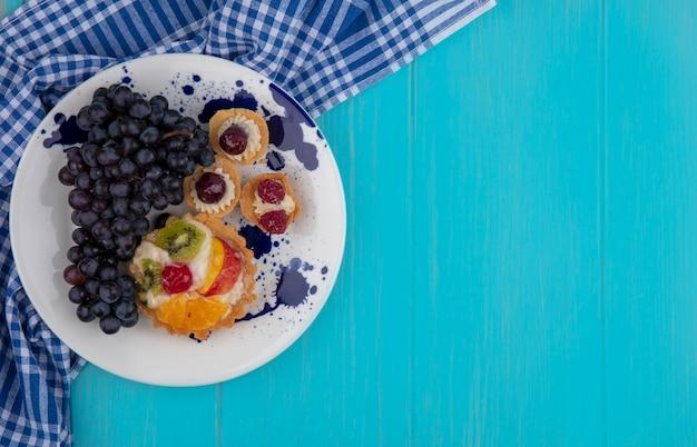 Bovenaanzicht van fruitige cupcakes en druivenmost in plaat op geruite doek op blauwe achtergrond met kopie ruimte