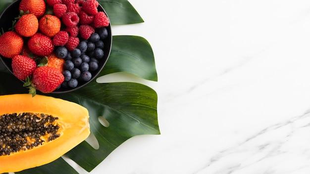 Bovenaanzicht van fruitschaal met papaja en kopie ruimte