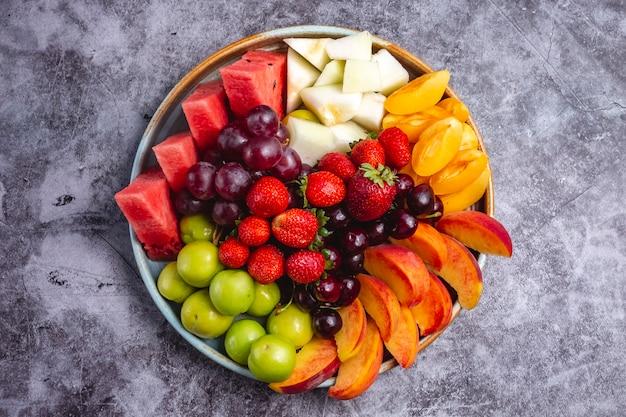 Bovenaanzicht van fruitschaal met watermeloen greengage pruim druif perzik abrikoos aardbei meloen en kers