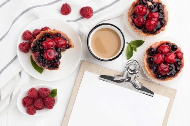 Bovenaanzicht van fruittaartjes met kladblok en koffie