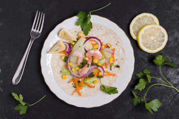 Bovenaanzicht van garnalen en ander eten op pitabroodje