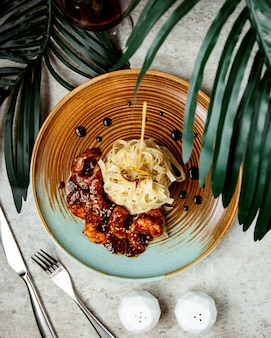 Bovenaanzicht van garnalen in teriyaki saus geserveerd met fettuccini
