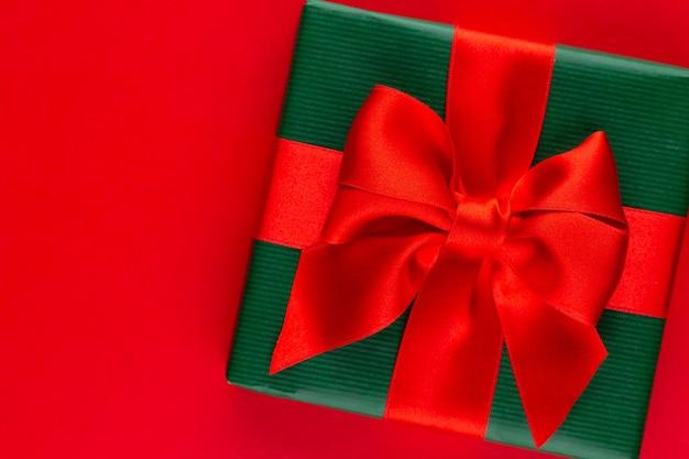 Bovenaanzicht van gearrangeerde verpakte kerst geschenkdozen met linten op rood tafelblad.