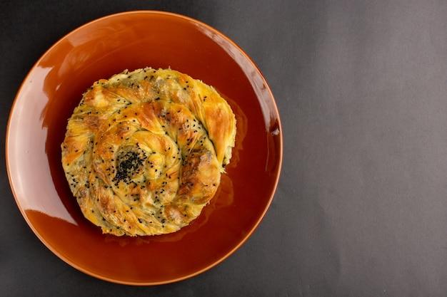 Bovenaanzicht van gebak met heerlijk deeg vleesmaaltijd binnen bruine plaat op donkere ondergrond
