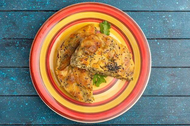 Bovenaanzicht van gebak met heerlijk deeg vleesmaaltijd binnen plaat op het blauwe rustieke oppervlak