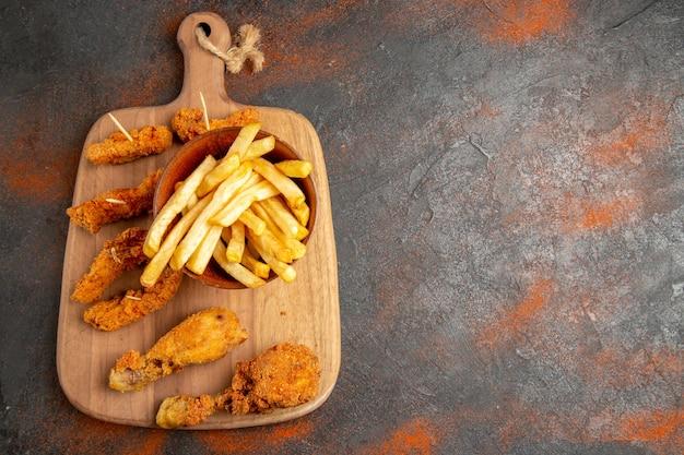 Bovenaanzicht van gebakken aardappel en kip op houten snijplank