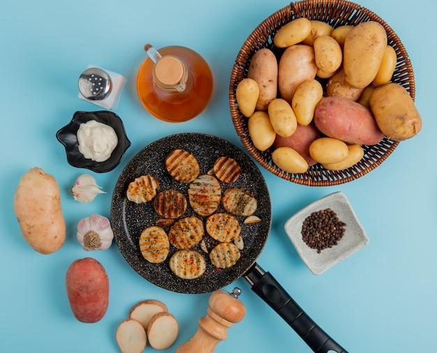 Bovenaanzicht van gebakken aardappel segmenten in koekenpan met ongekookte degenen in mand mayonaise knoflook zout zwarte peper en boter op blauw