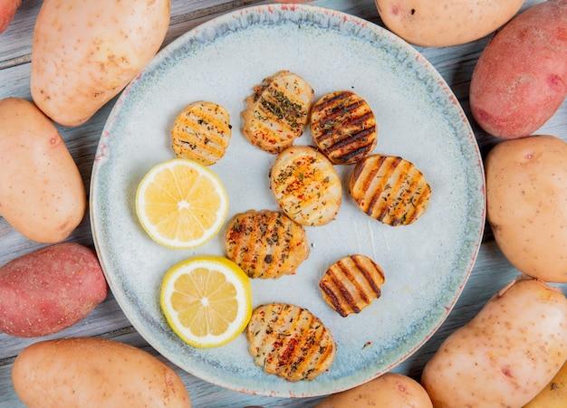 Bovenaanzicht van gebakken aardappelschijfjes en schijfjes citroen in plaat met witte en rode aardappelen rond op hout