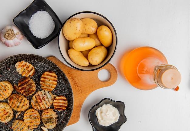 Bovenaanzicht van gebakken aardappelschijfjes in koekenpan op snijplank met ongekookte degenen in kom knoflook gesmolten boter mayonaise zout en zwarte peper op wit