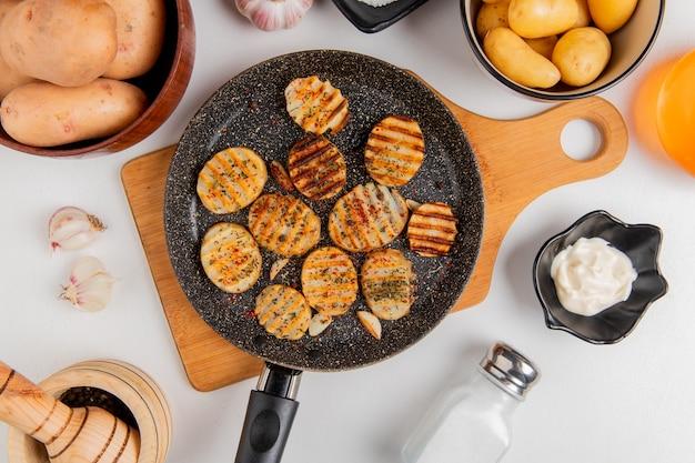 Bovenaanzicht van gebakken aardappelschijfjes in koekenpan op snijplank met ongekookte degenen in kommen knoflookboter mayonaise zout en zwarte peper op wit