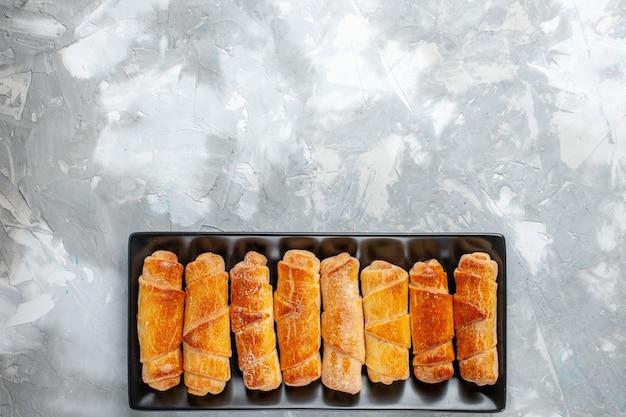 Bovenaanzicht van gebakken armbanden met vulling op grijs bureau, bangle gebak zoete suiker bakken