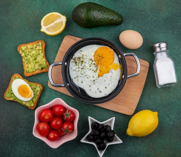 Bovenaanzicht van gebakken ei in een koekenpan op houten keukenbord met tomtoes citroen zwarte olijven op groen