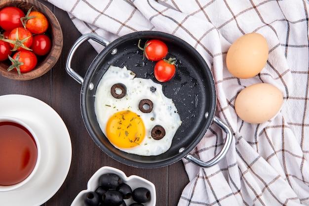Bovenaanzicht van gebakken ei met tomaten en olijven in pan en eieren op geruite doek met kommen tomaat en olijven kopje thee op hout
