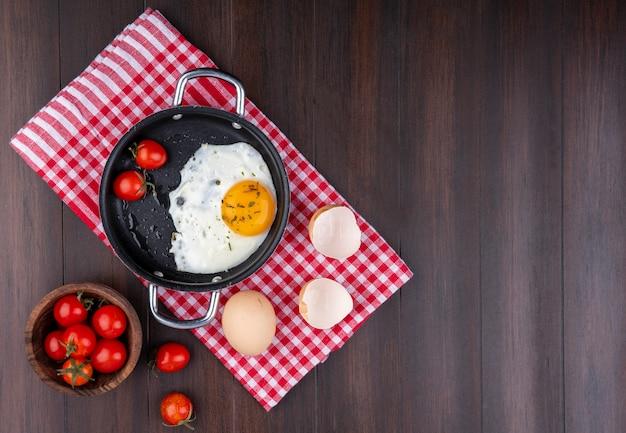Bovenaanzicht van gebakken ei met tomaten in pan en ei met schelp op geruite doek en kom tomaat op hout met kopie ruimte