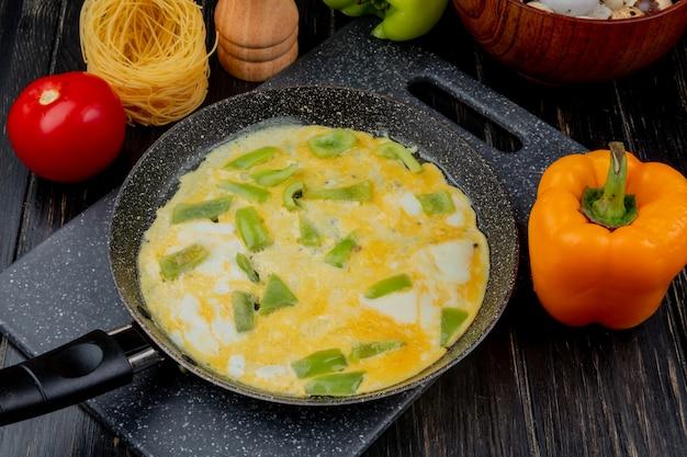 Bovenaanzicht van gebakken ei op een koekenpan met een oranje paprika met een tomaat op een houten achtergrond