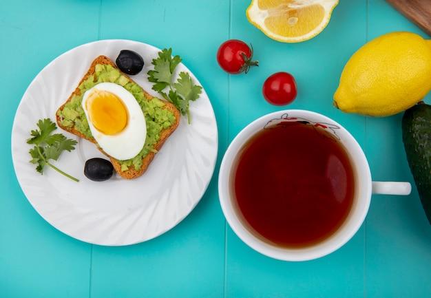Bovenaanzicht van gebakken ei op geroosterd sneetje brood met avocadopulp op witte plaat met zwarte olijven met een kopje thee op blauw