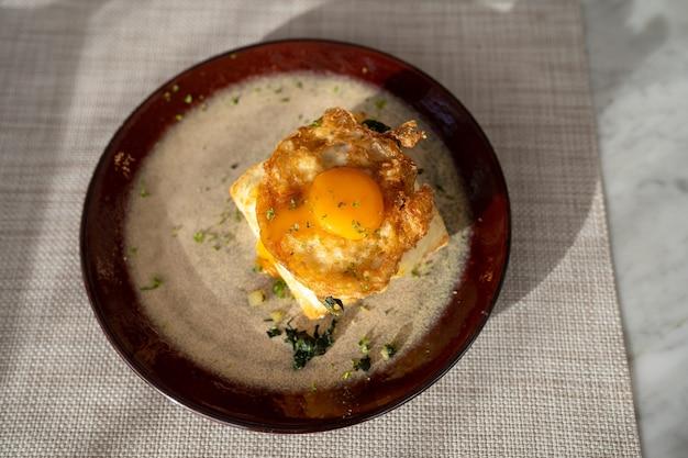 Bovenaanzicht van gebakken ei op sandwich op schotel voor ontbijt op tafel in de ochtend