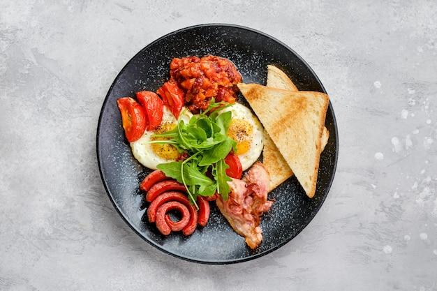 Bovenaanzicht van gebakken eieren met worst, spek, tomaten en bonen op een bord met toast
