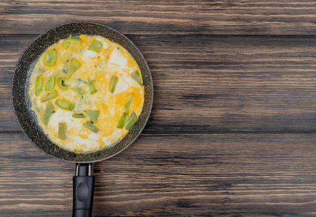 Bovenaanzicht van gebakken eieren op een zwarte koekenpan met groene paprika op een houten achtergrond met kopie ruimte